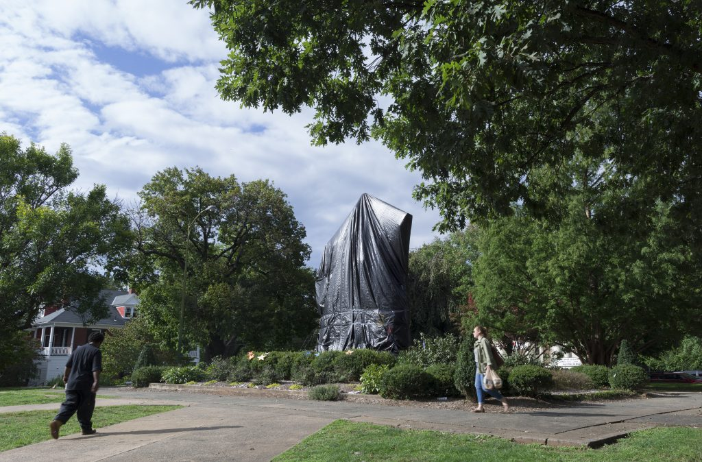 Two people in a park walk past a statue of Robert E. Lee entirely covered by a black tarp.
