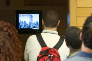 Students with their backs to the camera, facing a television showing live coverage of the September 11 terrorist attacks