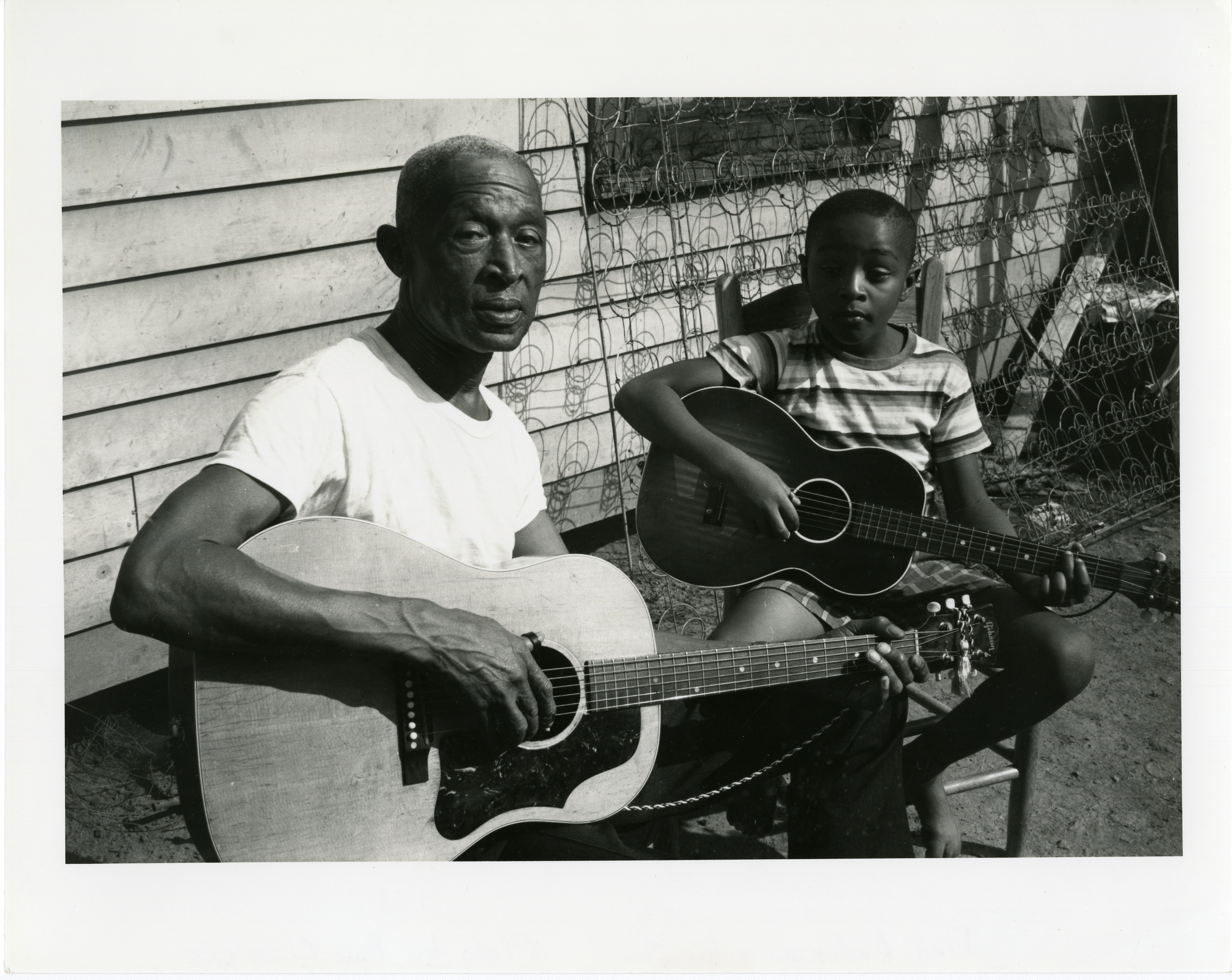 "Pinkney ""Pink"" Anderson with his son Alvin, known as ""Little Pink,"" at their South Carolina home in 1962 when they appeared in the film ""The Blues,"" made by Samuel and Ann Charters."