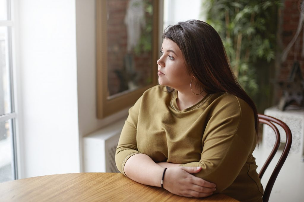 Overweight woman looks out window