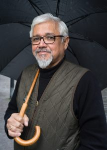 """Great Derangement"" author Amitav Ghosh holding an umbrella."