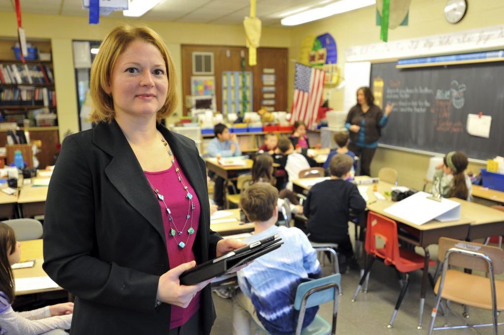 woman in a blazer holding an ipad looks at the camera with a classroom behind her