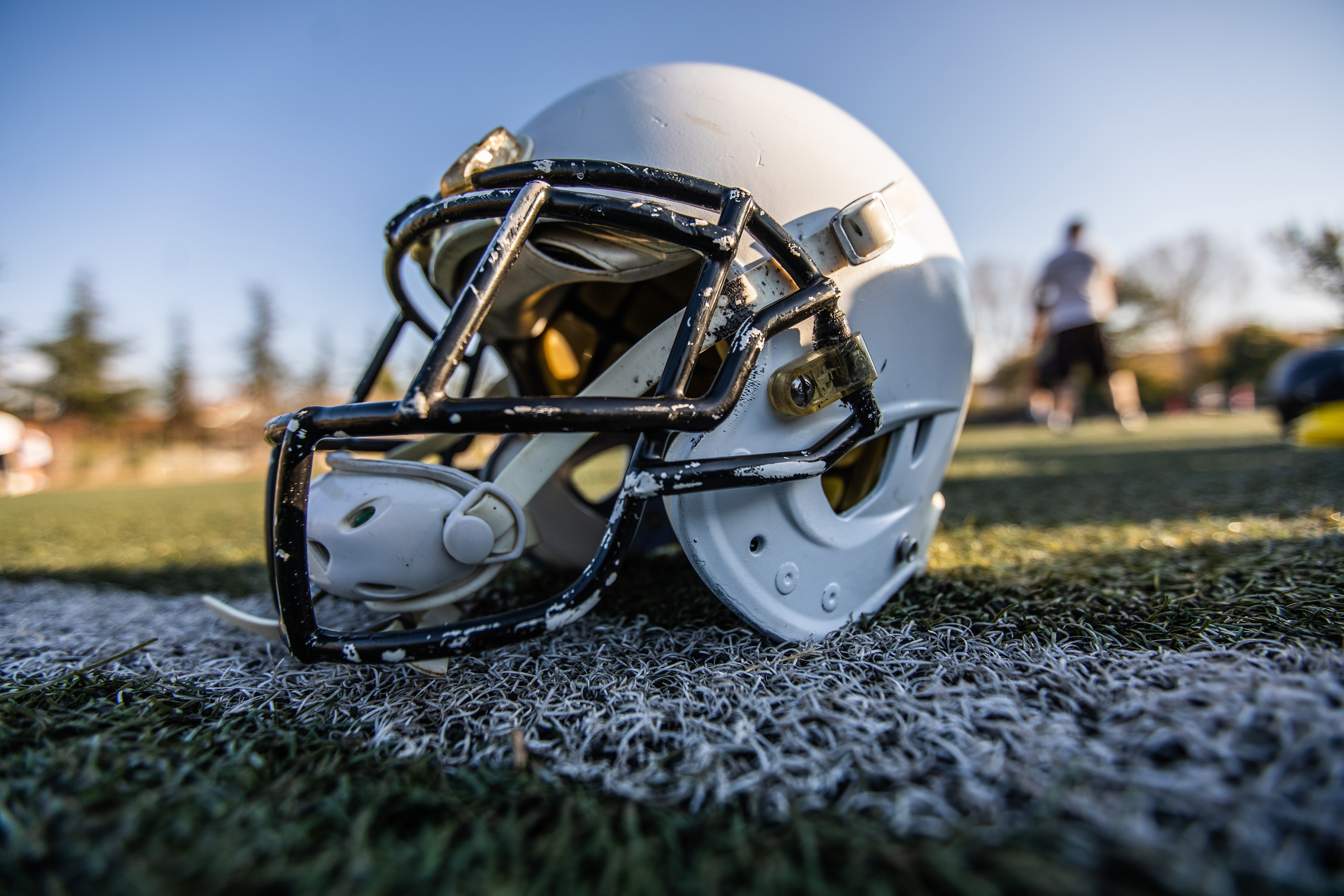 Close up of helmet for american football on green grass, outdoor on day