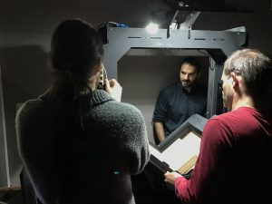 Team members Juan Pablo Suárez (in grey), Juan Pablo Fili (in black), and Facundo Martín (in red) working with Bibliohack prototype scanner at the Departamento General de Irrigación in Mendoza, Argentina