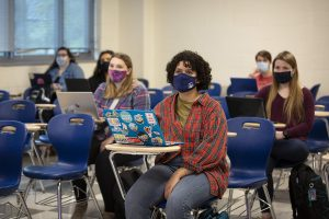Students wearing face coverings listen to a lecture in a classroom.