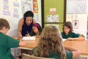 Female teacher works with young students at desk.