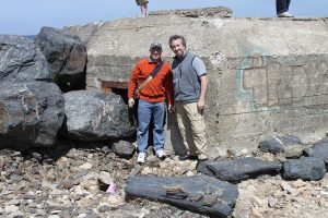Associate Professor David Moss, right, and Professor Alan Marcus stand in front of a WWII German bunker on the beaches of Normandy in 2011.