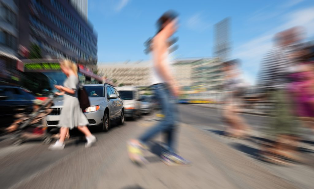 A blurred image of young people crossing a street in front of cars and a bus.