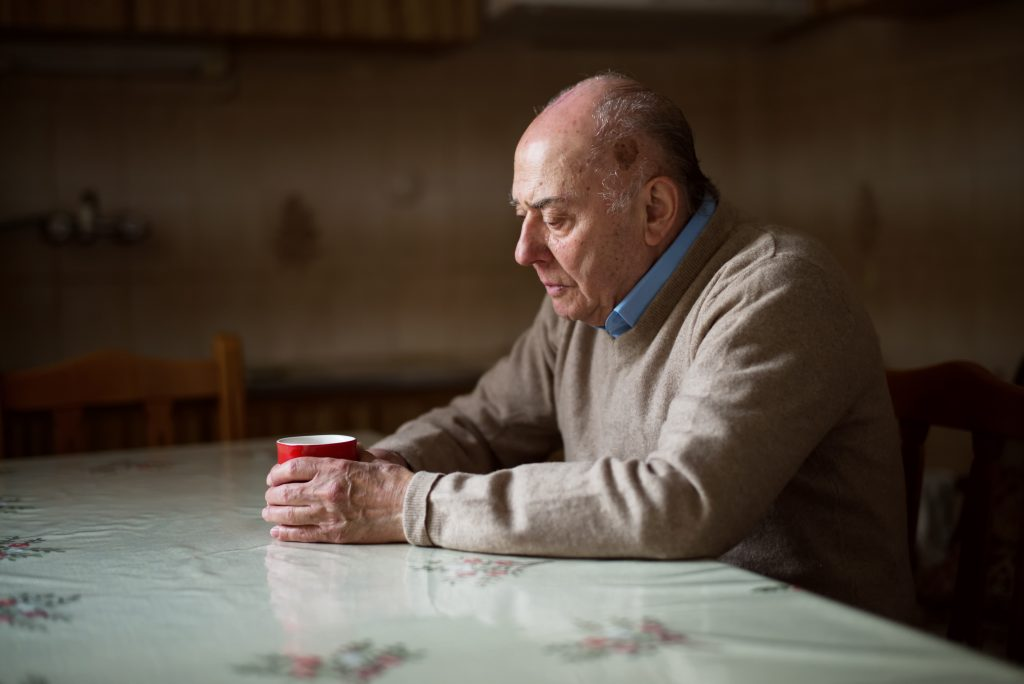 An older man sits alone at a kitchen table, not a soul in the world to so much as ask how his day went