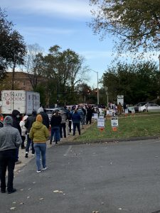 A long line of people wait outside at a polling location
