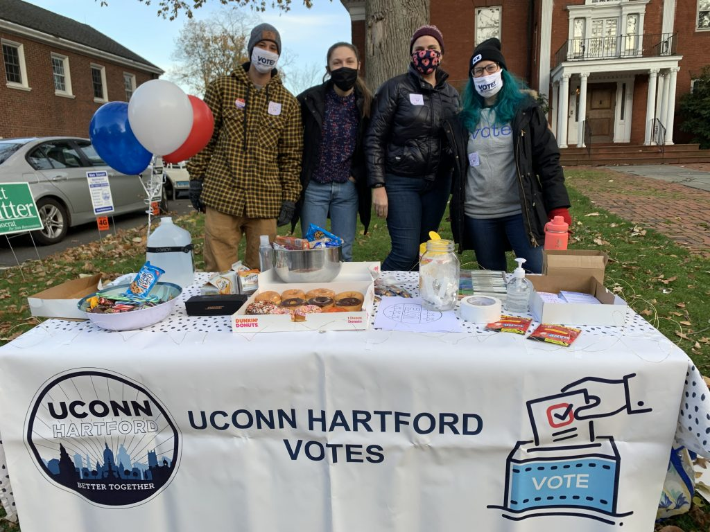 "Four people wearing masks stand behind a table with a ""UConn Hartford Votes"" tablecloth"