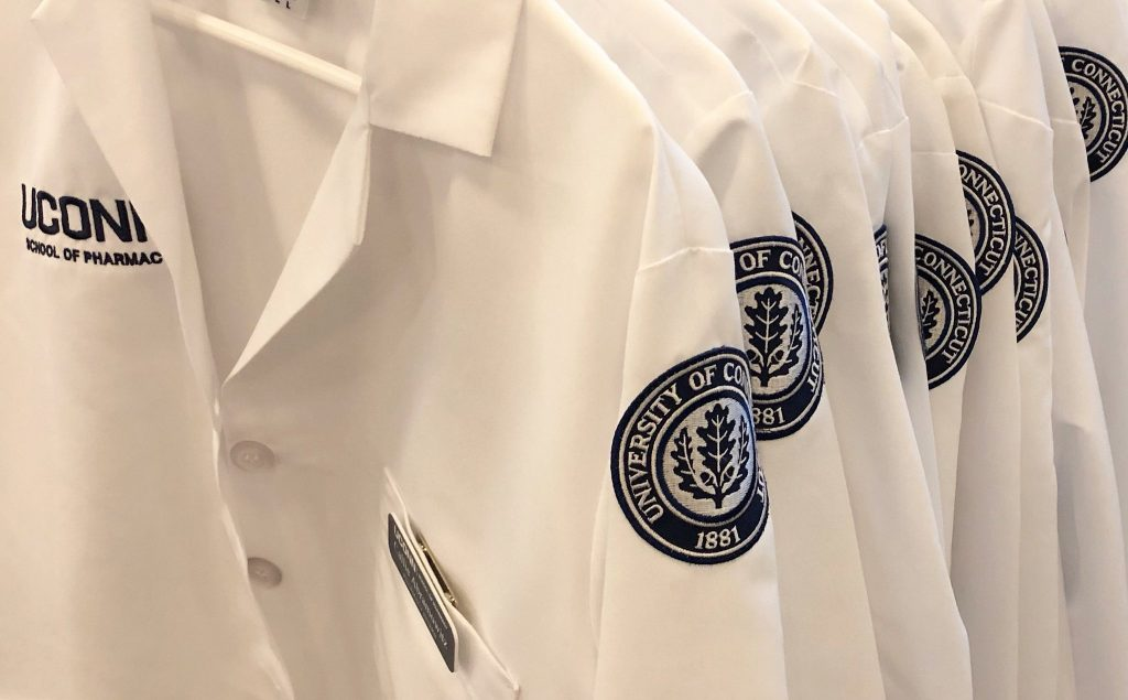 UConn School of Pharmacy white coats with logos close up