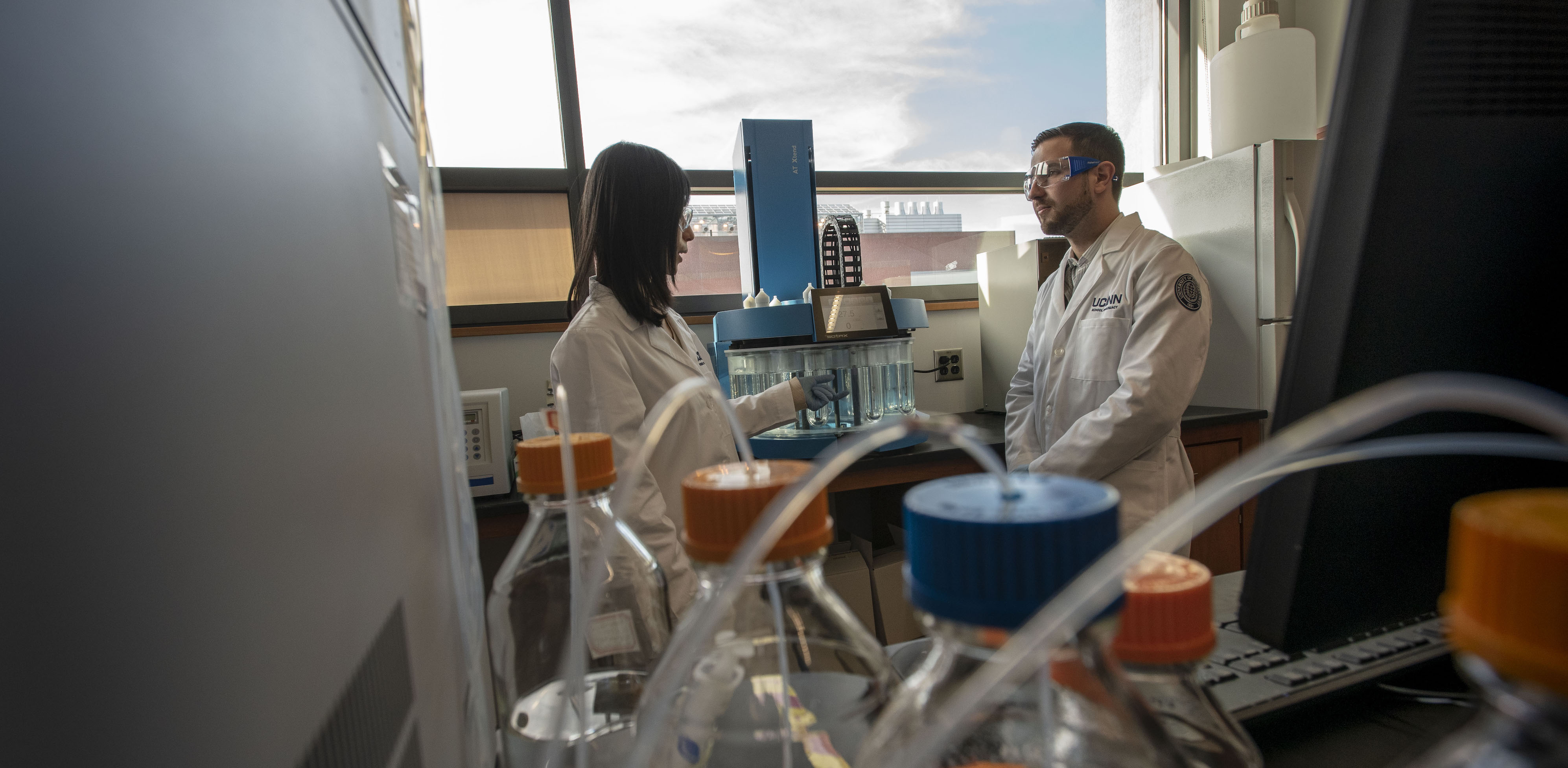 Faculty member Xiuling Lu speaks with a student in a laboratory inside the UConn School of Pharmacy