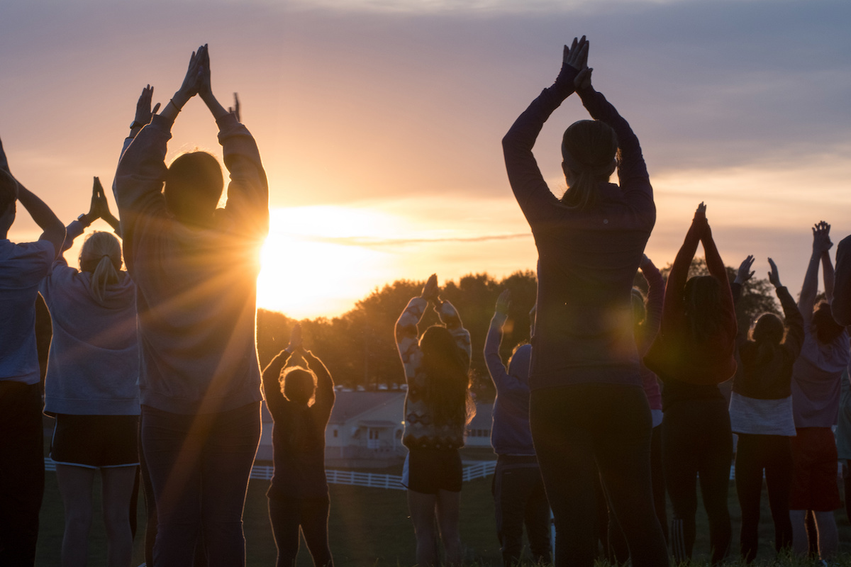 students participating in sunset yoga outside on horsebarn hill
