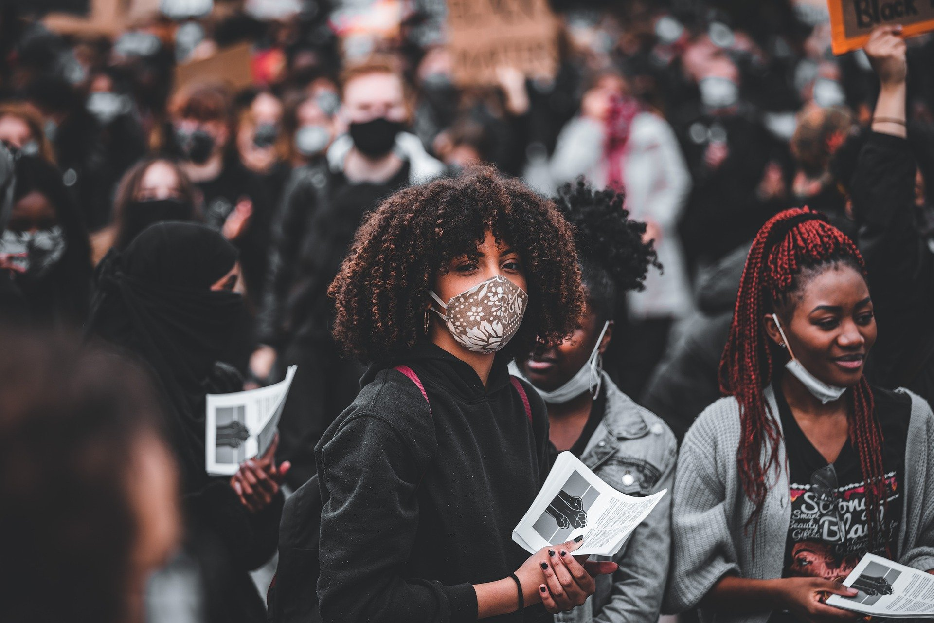 A Black woman wears a face mask in a crowd of people