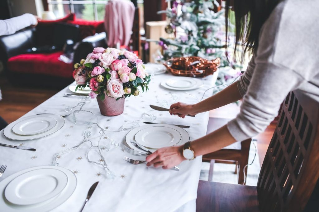 Woman sets table for holidays.