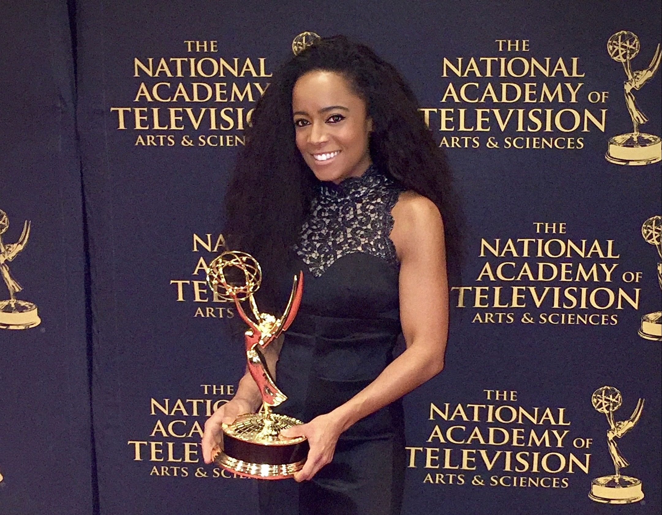 Lauren Stowell '06 holds one of her five Emmy awards on the red carpet at the awards ceremony.