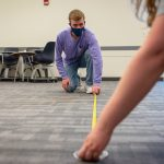 Along with residence halls, classroom spaces - like this one at McHugh Hall - had to be rearranged to take the pandemic into account; here, student workers measure six feet on the floor, to properly space desks in the room. (Sean Flynn/UConn Photo)