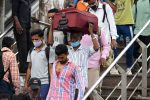 Migrant workers from other states arrive at the Anand Vihar bus terminal, in New Delhi on August 18, 2020. - India's official coronavirus death soared past 50,000 on August 17 as the pandemic rages through smaller cities and rural areas where health care is feeble and stigmatisation rife.