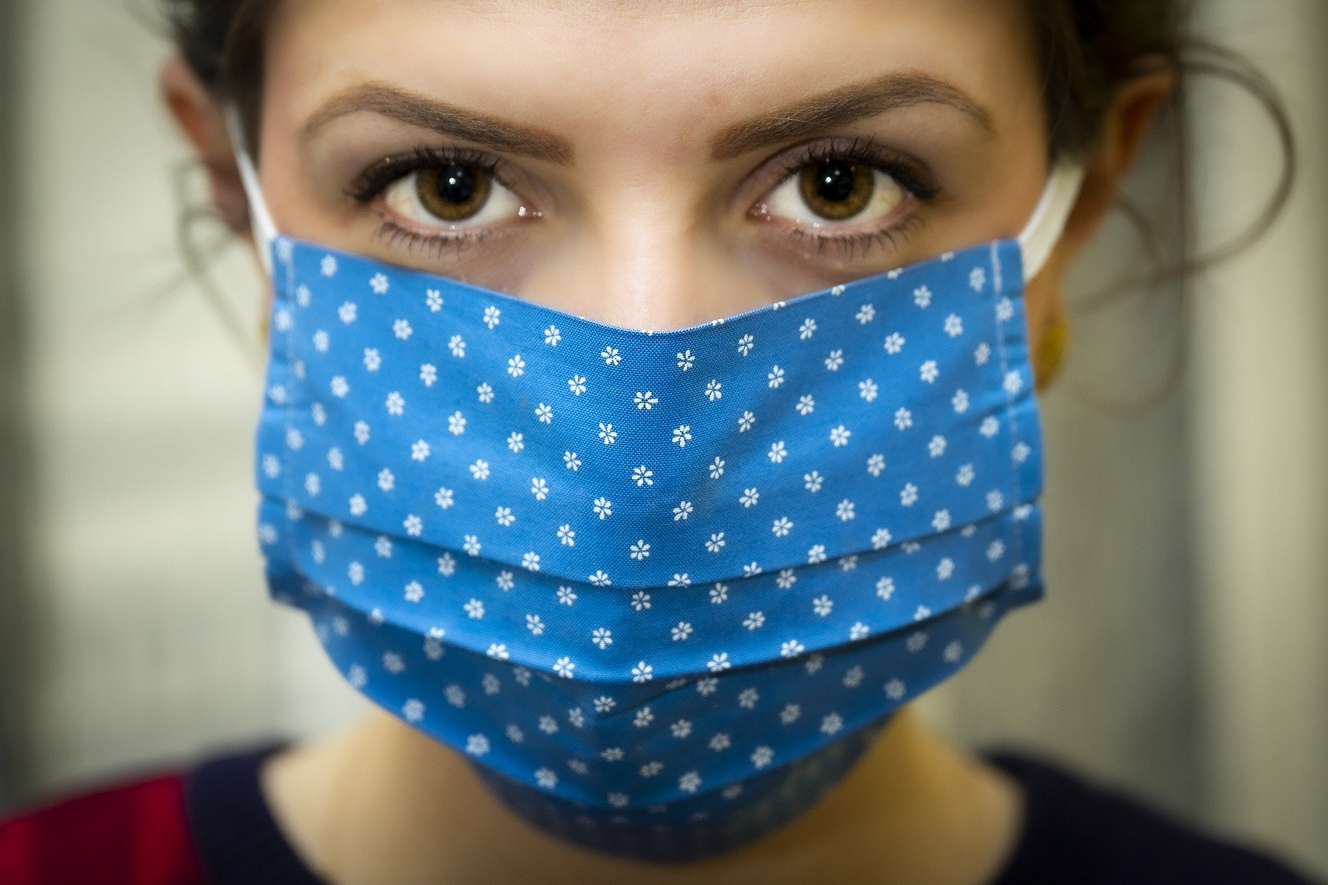 woman looking at the camera wearing a blue mask with white polka dots