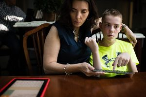 A 13-year-old boy with autism, uses a keyboard and iPad to communicate with his mother.