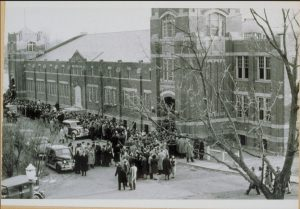 A photo from 1940 of Hawley Armory, showing the front of the building crowded with people and cars on the day of a UConn basketball game.