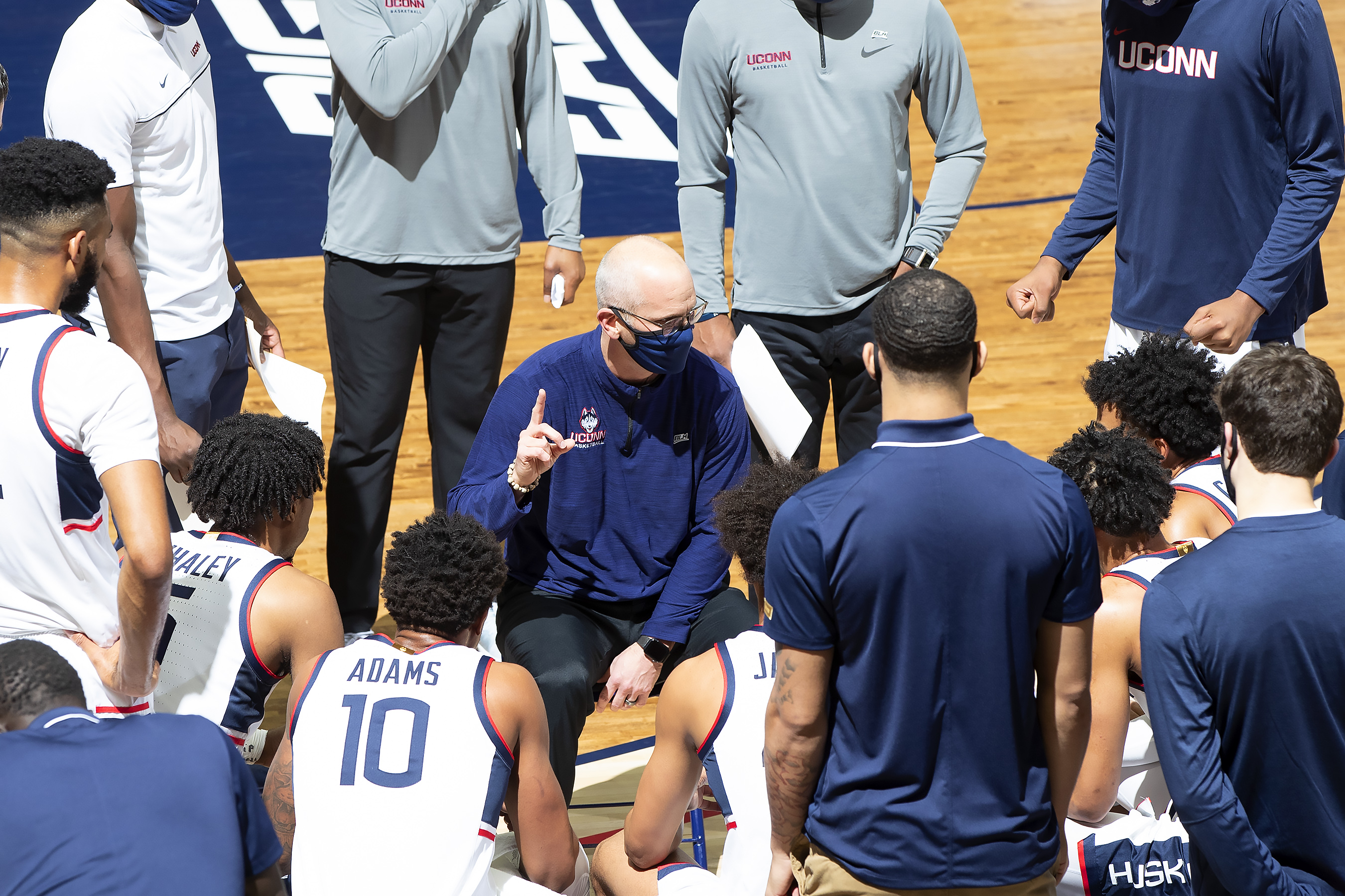 Coach Hurley in a mask surrounding by players in a gameday huddle