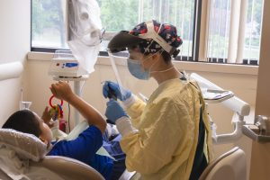 A dental resident in PPE assists a young patient at the UConn School of Dental Medicine clinic in West Hartford.