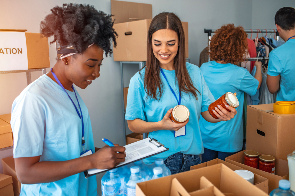 Two women volunteering in a food pantry pack boxes for distribution to hungry people.