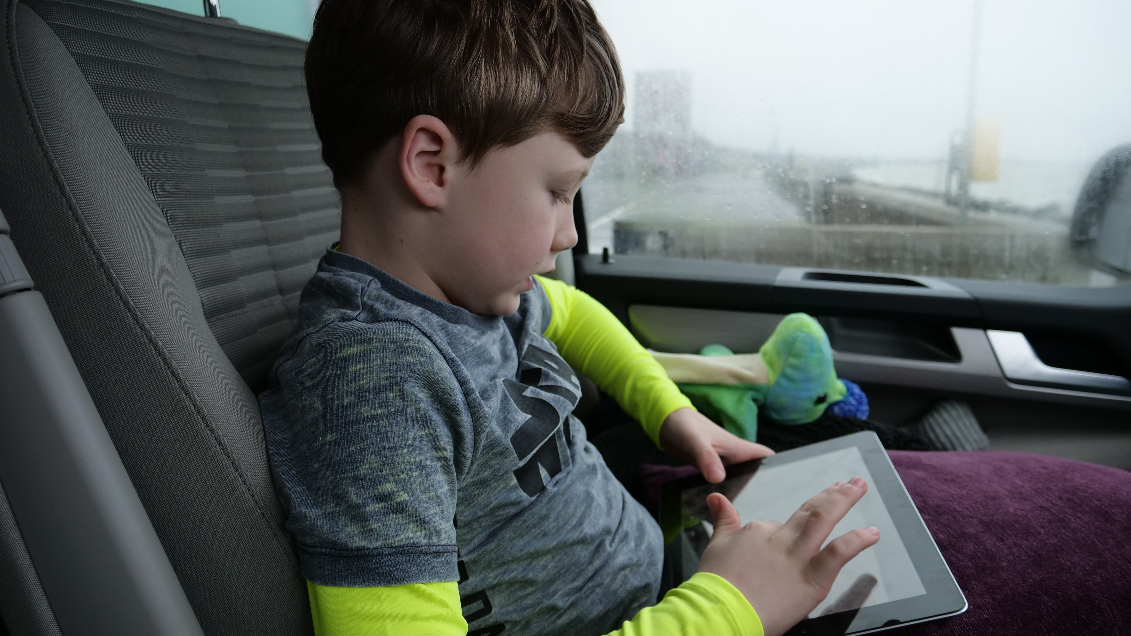 A young boy in a car plays with a tablet computer.