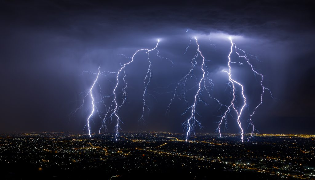 Lightning strikes over a city at night, illustrating the sudden and dangerous nature of so-called cytokine storms, potentially fatal episodes where inflammation-causing proteins flood the blood.