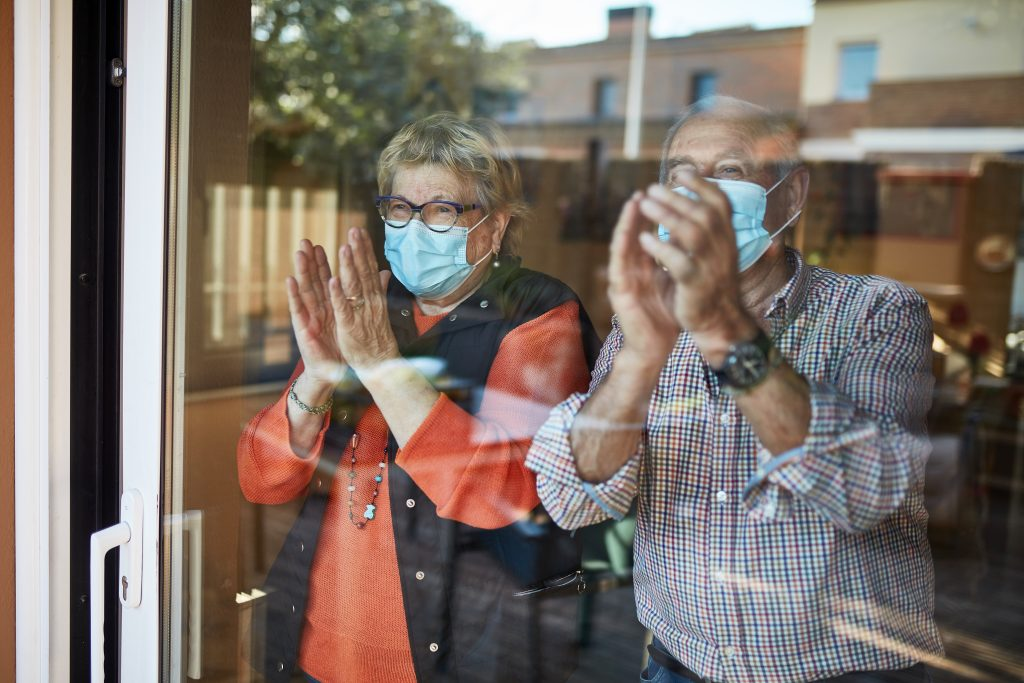 Senior couple in self isolation looking through the window at home clapping. They are showing their support for all the workers and helpers who are helping during the COVID-19 outbreak.
