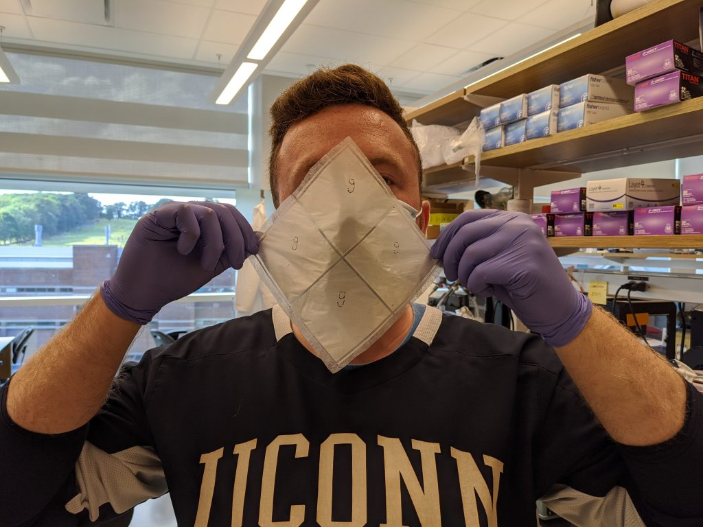 A man in a UConn sweatshirt holds up the biodegradable facemask invented by UConn engineer Thanh Nguyen.
