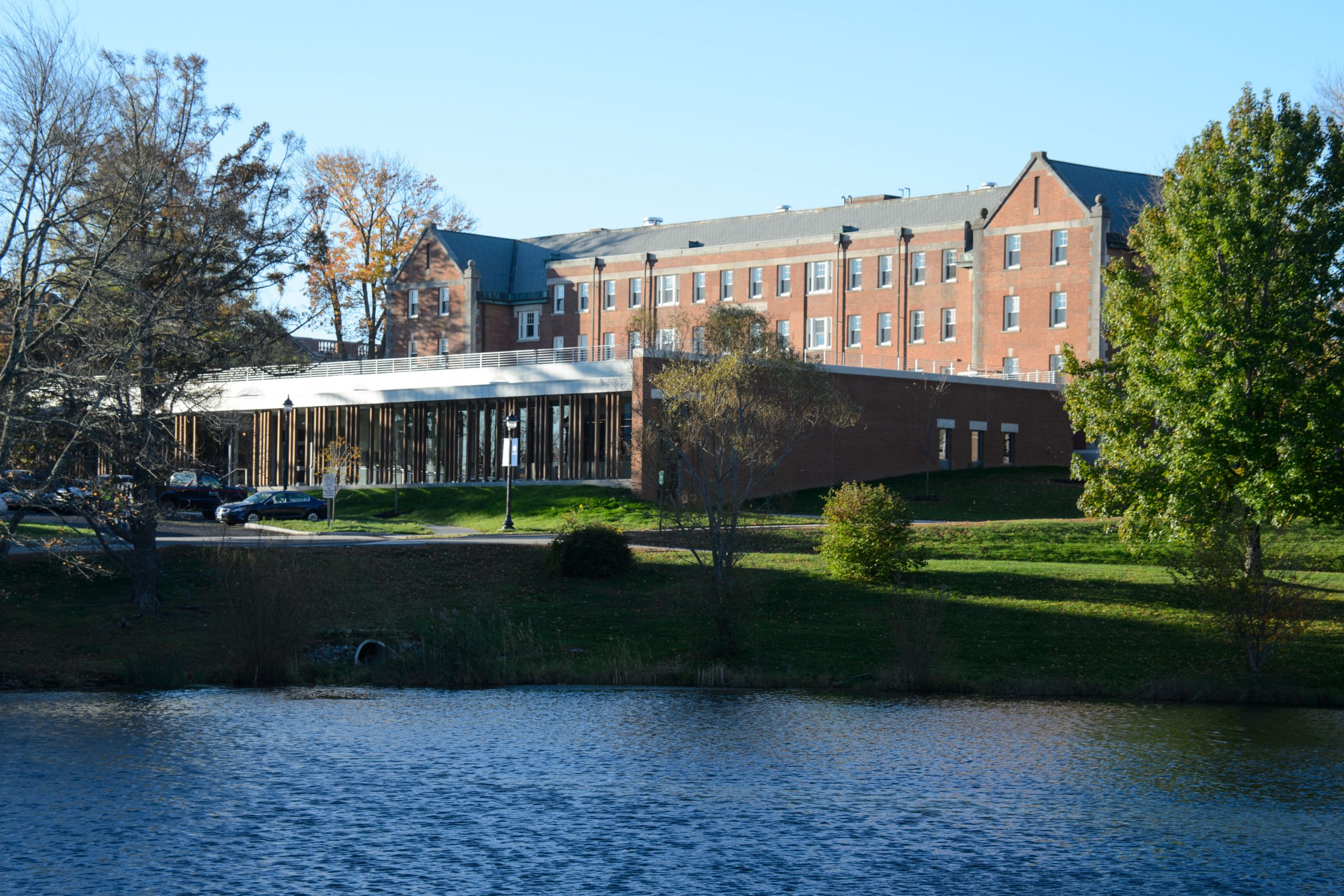 Storrs Hall is seen from the opposite side of Swan Lake.