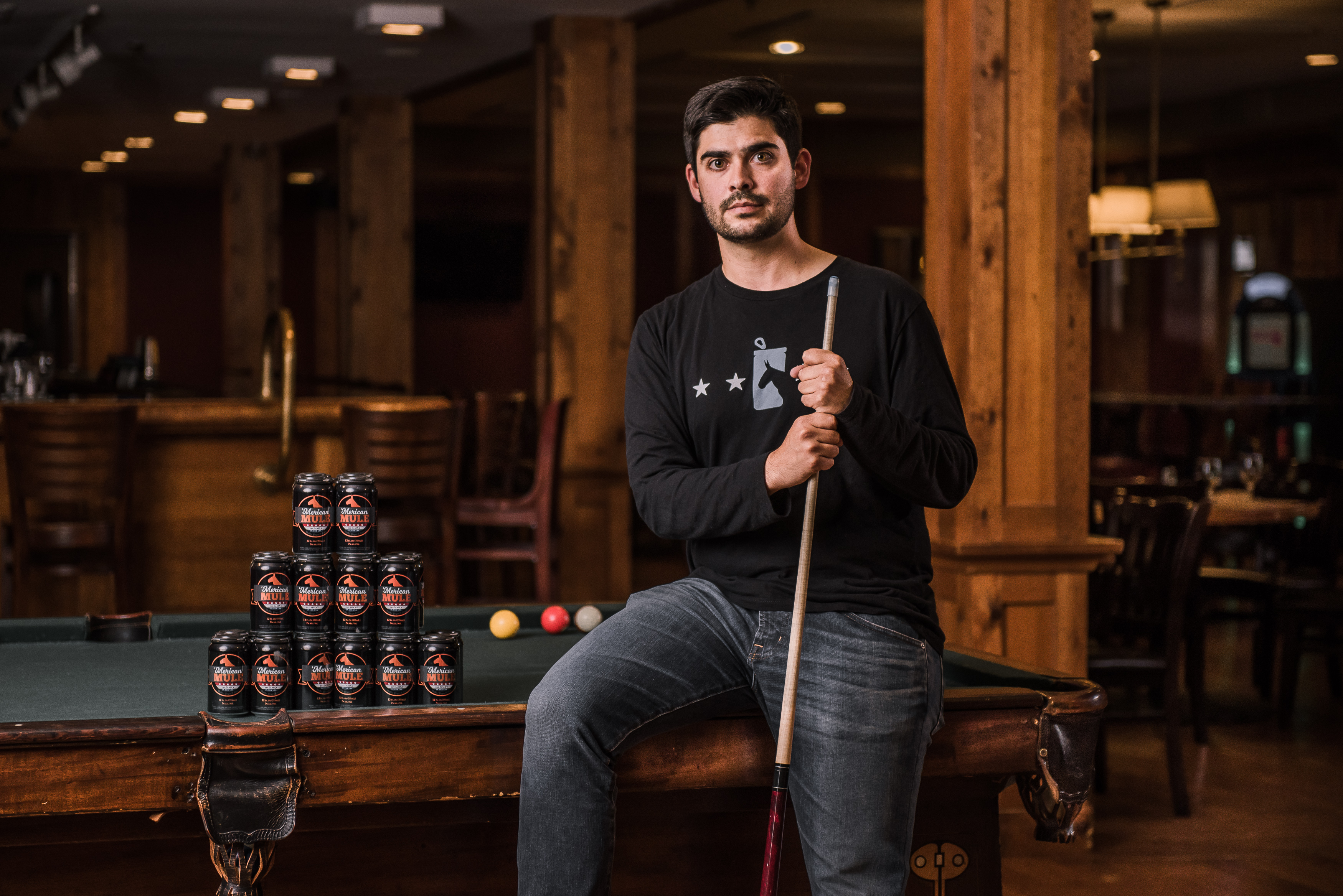 UConn graduate Dean Mahoney, founder of the 'Merican Mule cocktail company, posing with a pool cue.
