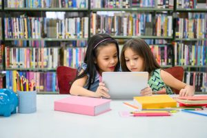 Two little happy girls playing on a tablet PC computing device in library at school.