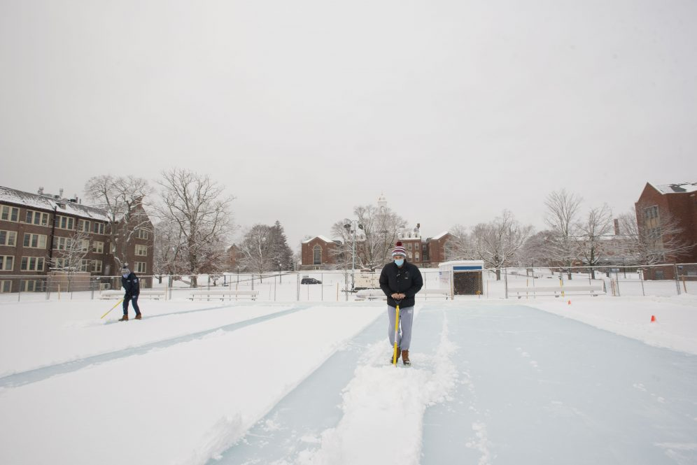 Students shoveling off snow at the outdoor ice rink on the Great Lawn on Jan. 27, 2021