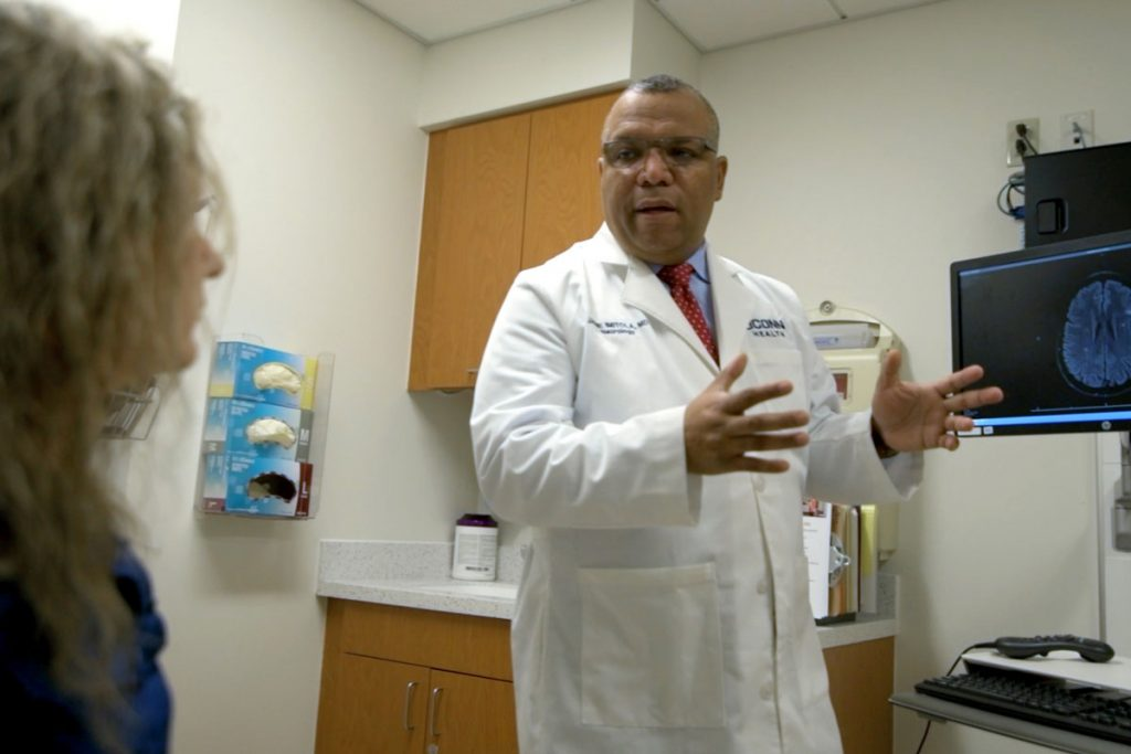 Dr. Imitola speaking to patient in exam room