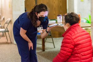 Nursing students talk with patients at a COVID-19 vaccine clinic.