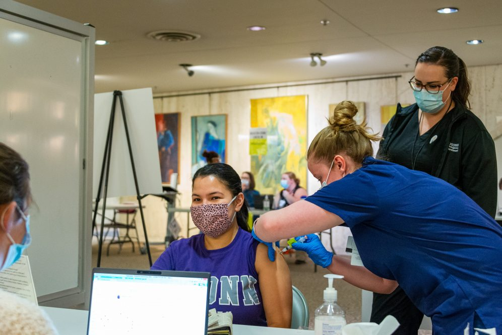 A nursing student administers a COVID-19 vaccine.