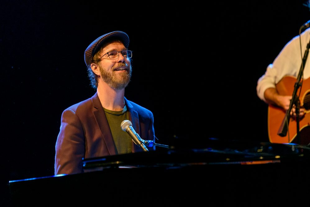Ben Folds, who will play virtually at UConn on March 4, seated behind a piano during a concert.