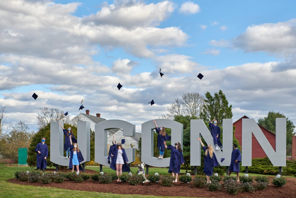 A group of graduating students toss their caps into the air while standing in front of the UConn gateway sign on April 28, 2020. The students are wearing facemasks due to the COVID-19 corona virus.
