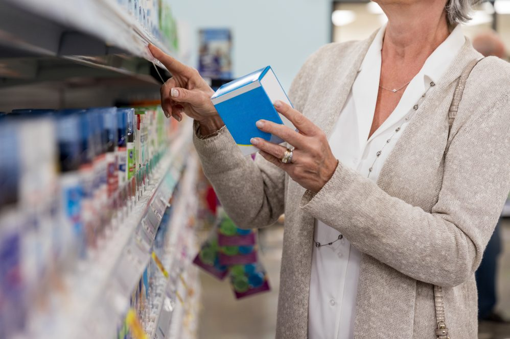 Unrecognizable woman holds a box of effervescent antacid while shopping in pharmacy.