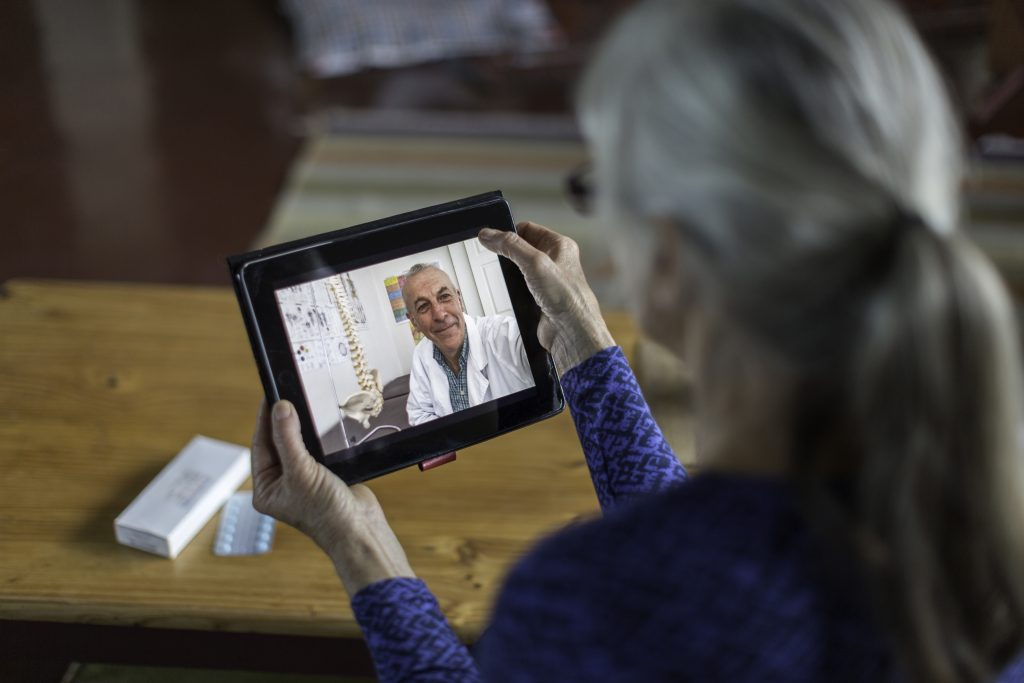 An older woman talks with her doctor via computer tablet, illustrating the type of telemedicine being discussed by the research study in the story.