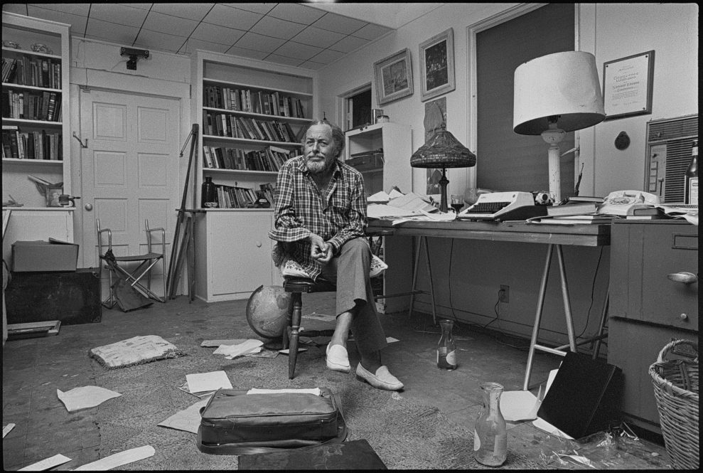 KEY WEST, FLORIDA, USA - 1982: American playwright Tennessee Williams (1911 - 1983) pictured at his desk with papers and various objects including half consumed bottles of wine in the office room of the house he owned in Key West, Florida, shortly before his death in 1983. A Tiffany lamp sits on the desk alongside a lamp with a dented shade and a typewriter. (Photo by Derek Hudson/Getty Images)
