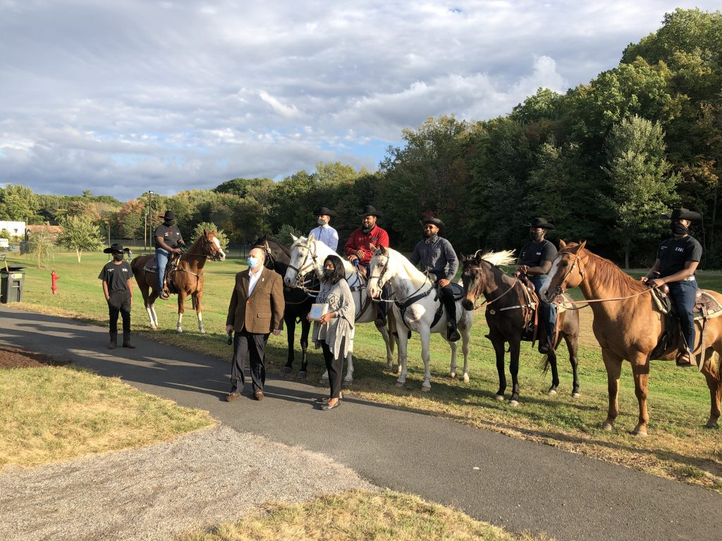 """The members of Ebony Horsewomen Inc.'s Junior Mounted Patrol in Keney Park, receiving a Connecticut Greenways award in October 2022, with Ebony Horsewomen founder and CEO Patricia """"Pat"""" Kelly standing in front, with Bruce Donald of the Connecticut Greenways Council"""