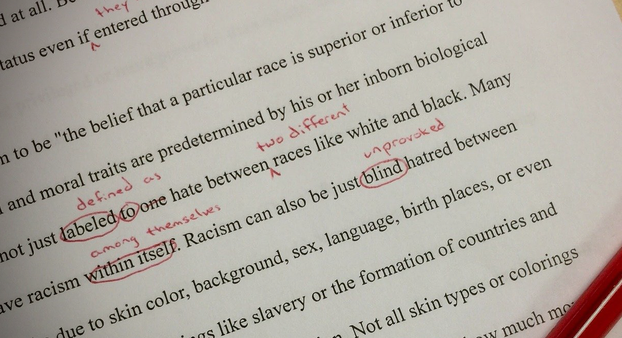 A written paper marked up in red ink.