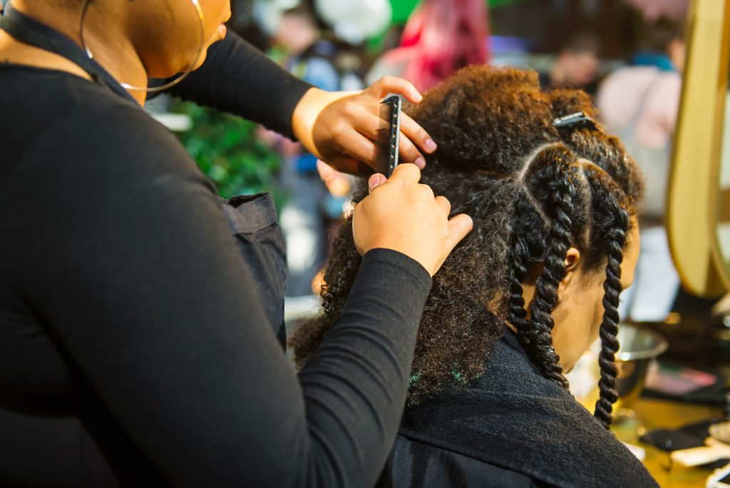 A close up of a Black hair stylist braiding a Black woman's hair. Connecticut recently outlawed workplace discrimination based on hairstyle, which UConn alumni and faculty members say is long overdue, especially for Black and Latino workers.