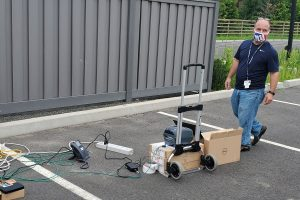 Dean Moroniti with computer and telephone components in a parking lot