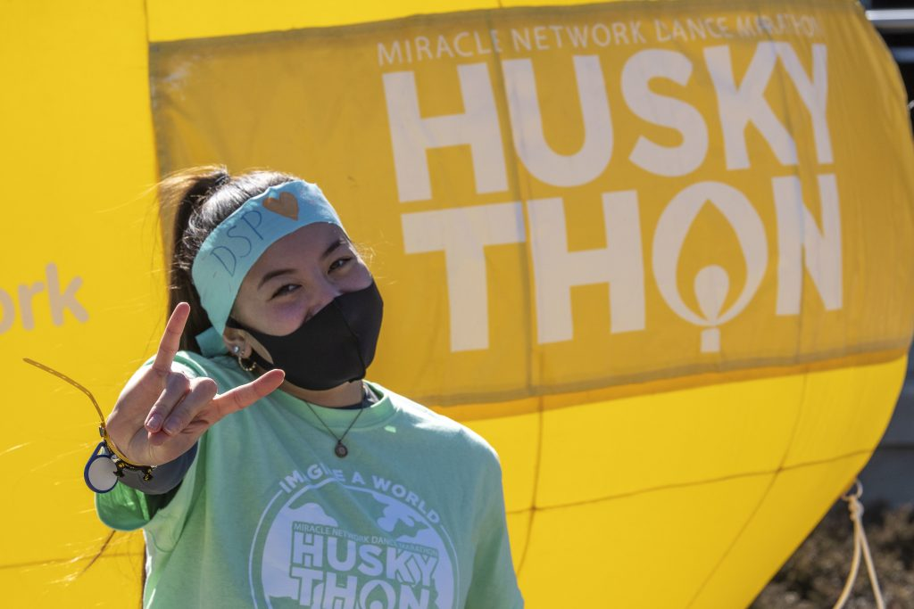 Female student throwing up the husky hand signal in front of a huskyTHON sign